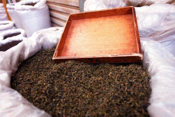 Thé noir d'Assam dans un grand bac, ressemble à du tabac brut